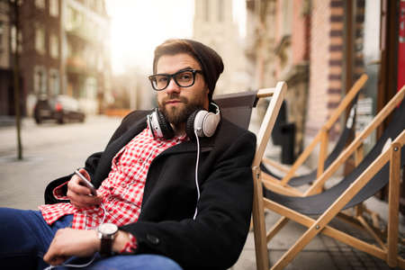 bespectacled man: Man relaxing in front of cafe