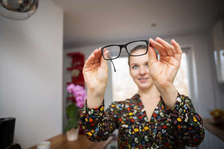 flowered: A photo of young woman in flowered shirt looking through her glasses.