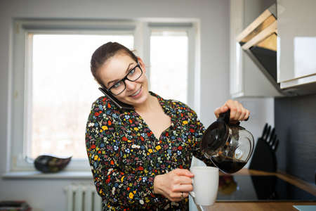 flowered: A photo of young woman in flowered shirt talking on the mobile and pouring coffee to the cup.
