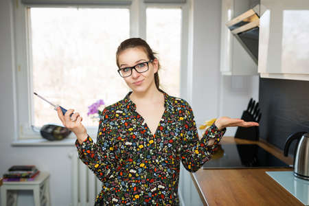 flowered: A photo of young woman in flowered shirt standing in the kitchen with a screwdriver in her hand. Stock Photo