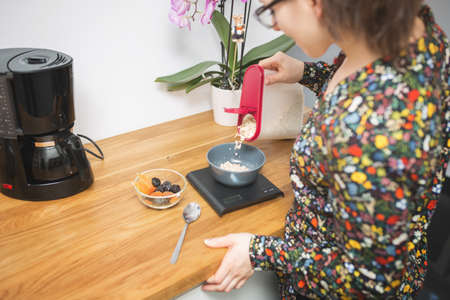 flowered: A photo of young woman in flowered shirt making breakfast. Shes pouring cornflakes into the bowl and weighing them.