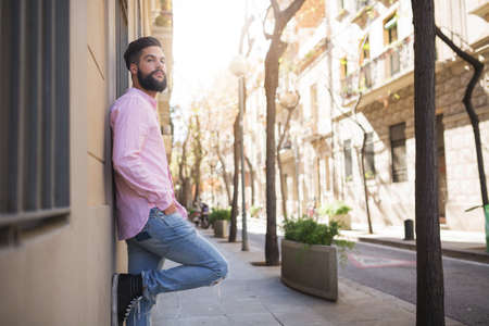looking ahead: A photo of young man leaning against wall of some building and looking ahead. Stock Photo