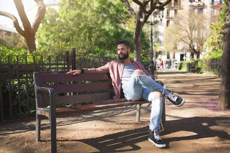 free time: A photo of young man sitting on the bench in the park and enjoying his free time.