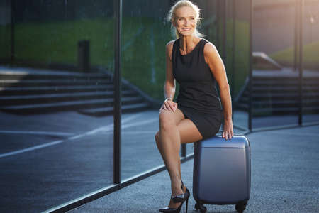 Happy businesswoman sitting on suitcase