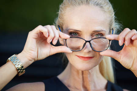 glad: Glad businesswoman holding spectacles Stock Photo