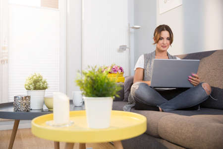 cosy: Woman on couch with laptop