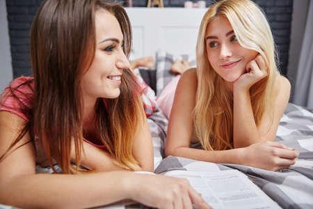 female magazine: Female friends reading magazine together