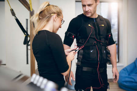 Female trainer connecting cables on sportsman ems suit Stock Photo