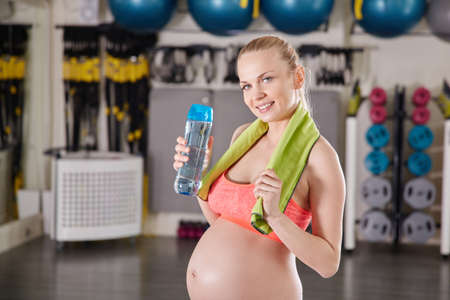 Happy pregnant woman standing at gym holding bottle of water