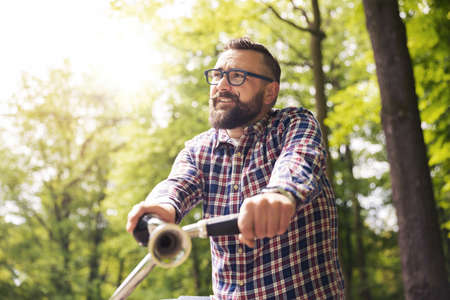 Young modern man riding bike in park looking away Stock Photo