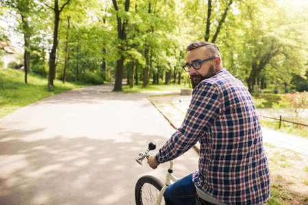 Young modern man turning back on bicycle Stock Photo
