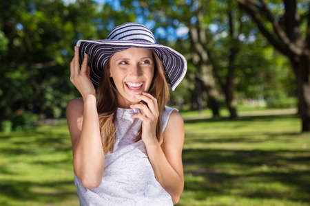 easygoing: Pretty carefree woman in hat outside looking away Stock Photo