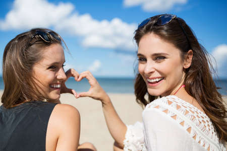 Two young women on beach making heart sign laughing Stock Photo