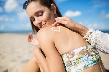 relaciones sexuales: Hermosa chica en la playa y su amiga aplicando aceite bronceador sobre ella