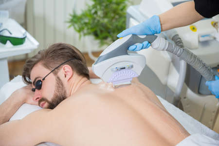 Men lying at beauticians during laser back hair removal therapy
