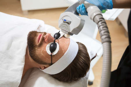 Man at beauticians during laser anti-aging therapy Stock Photo