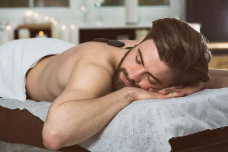 lastone therapy: Man relaxing in spa at hot stones massage