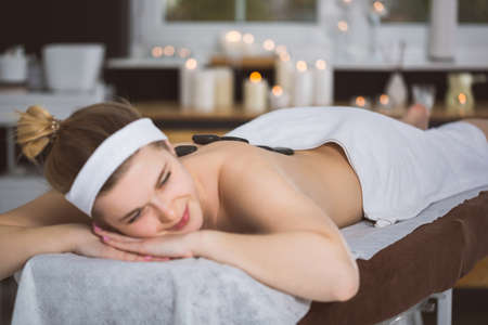 lastone therapy: Blonde woman relaxing in spa with hot stones on her back Stock Photo