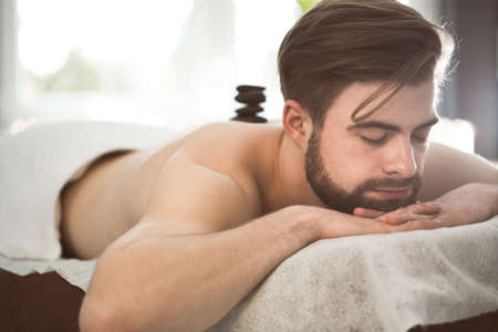 Man relaxing in spa at hot stones massage
