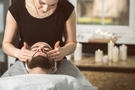 Man at beauticians during gold mask anti-aging therapy Stock Photo
