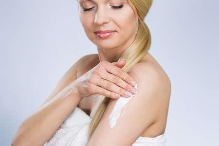 Woman moistening her skin with cream Stock Photo