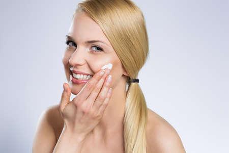 Beautiful happy woman applying cream on face