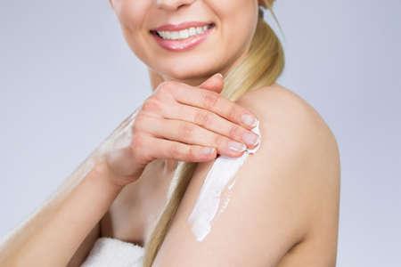 Happy woman applying cream on arm Stock Photo