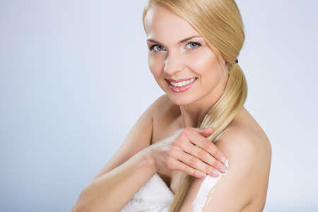Beautiful happy woman applying cream on arm