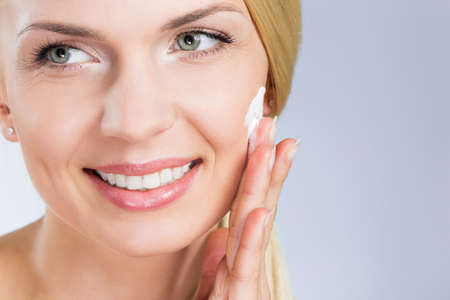 Happy woman applying cream on face looking away Stock Photo