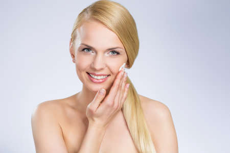 Young pretty woman applying cream on face Stock Photo