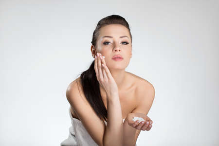 Beautiful woman in towel applying face cream