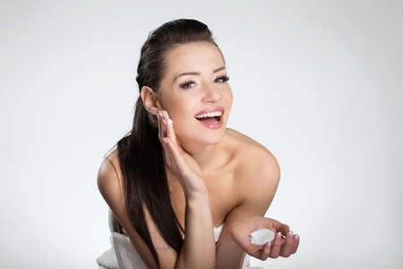 Beautiful happy woman moistening face with cream Stock Photo