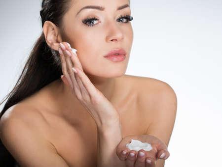 Beautiful serious woman applying cream on face Stock Photo