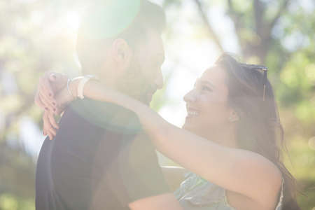 other side: Young happy couple in love embracing in sunlight Stock Photo
