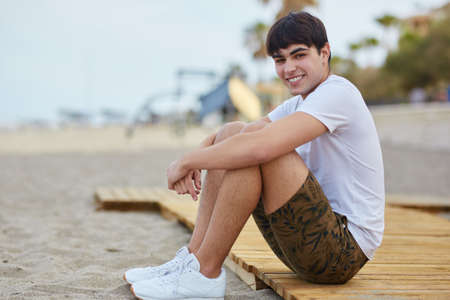 Young happy man sitting on beach smiling Stock Photo