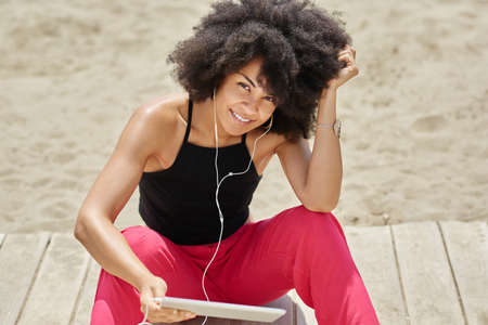 Afro american woman listening music on tablet smiling