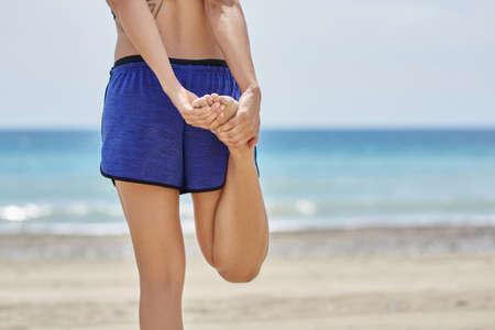 Sportswoman stretching her legs on beach Stock Photo