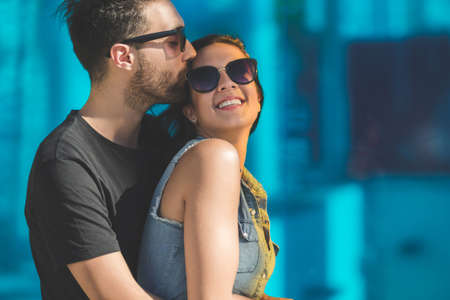 Portrait of man in sunglasses embracing and kissing happy girlfriend Stock Photo
