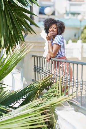 Pretty afro american woman leaning against fence laughing Stock Photo