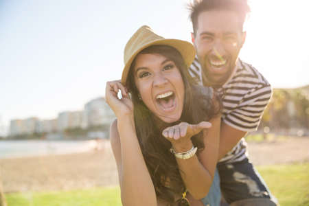 Happy woman in hat laughing with her boyfriend outside
