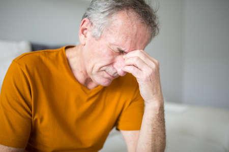 Senior man suffering from migraine