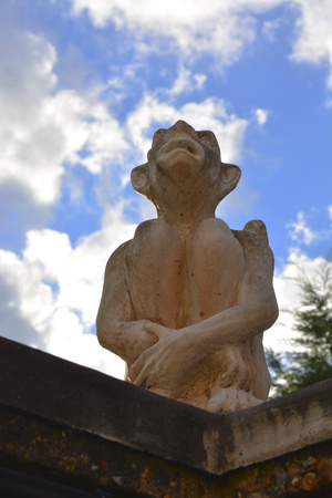 Crouching Gargoyle and Cloudy Blue Sky