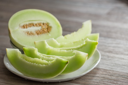 Cut pieces of honeydew melon on white ceramic plate on wooden background