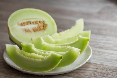 Schneiden Sie Honigmelone auf weißem Keramikteller auf Holzuntergrund Standard-Bild