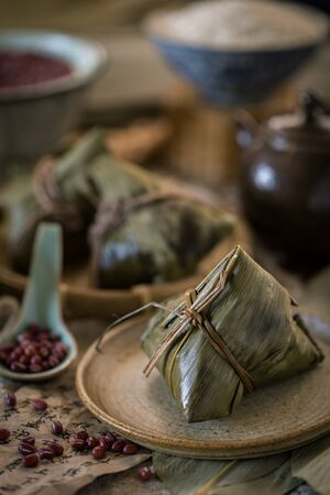 Glutinous rice dumplings with red bean azuki bean wrapped with bamboo leaves with traditional Chinese style setting as background