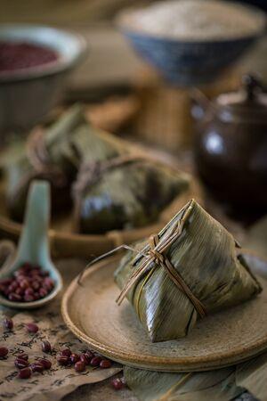 糯米饺子用红豆azuki豆包裹与竹子叶子与传统中国样式设置作为背景