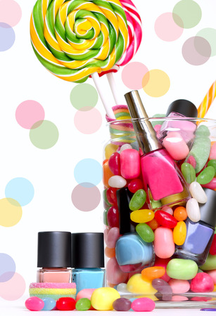 Jelly: Jelly beans sugar candies and colorful nail polish in a jar isolated on white with dots