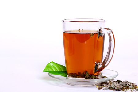 Cup of fresh herbal tea on white