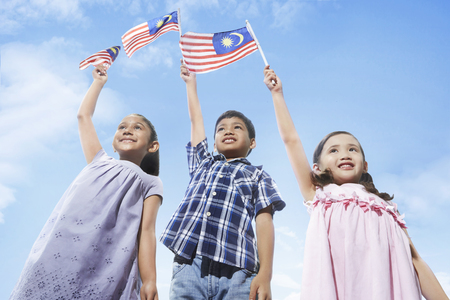 Asian young kids holding up flags of Malaysia LANG_EVOIMAGES
