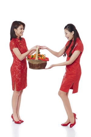 Young women holding mandarin oranges in a bamboo basket